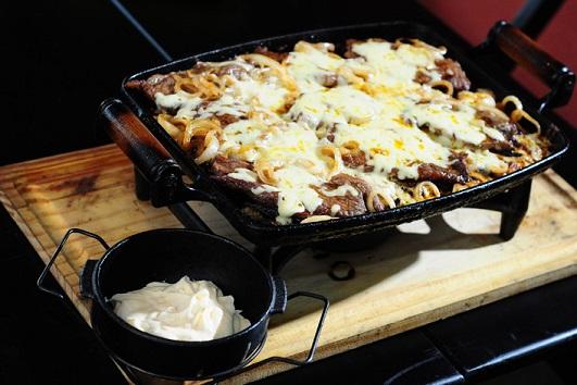 Mistura Fina: Picanha no rechaud com temperos especiais e maionese, acompanhado com cebola coberto com queijo derretido